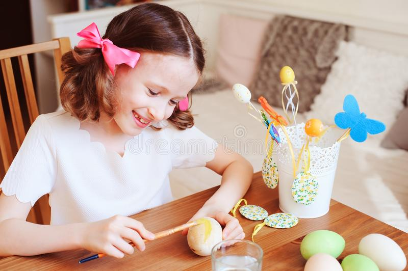 Happy 7 years old kid girl painting easter eggs. Easter craft and holiday preparations royalty free stock photos