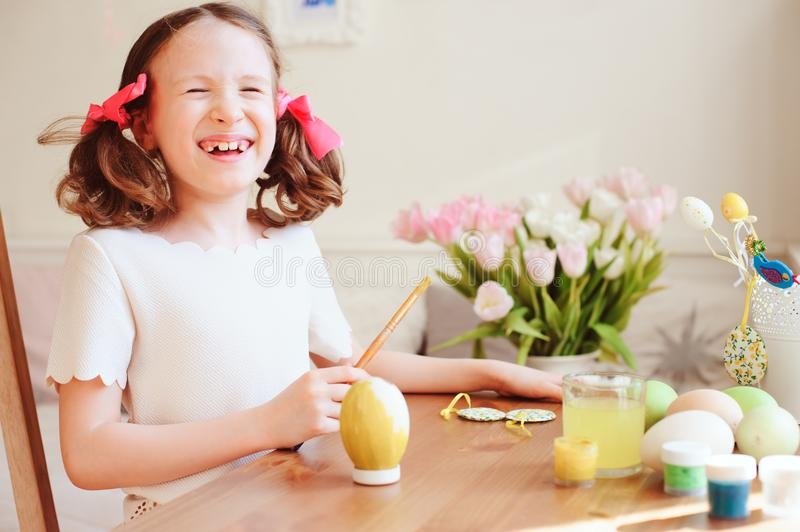 Happy 7 years old kid girl painting easter eggs. Easter craft and holiday preparations royalty free stock photography