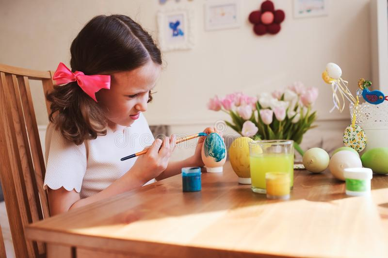 Happy 7 years old kid girl painting easter eggs. Easter craft and holiday preparations royalty free stock images