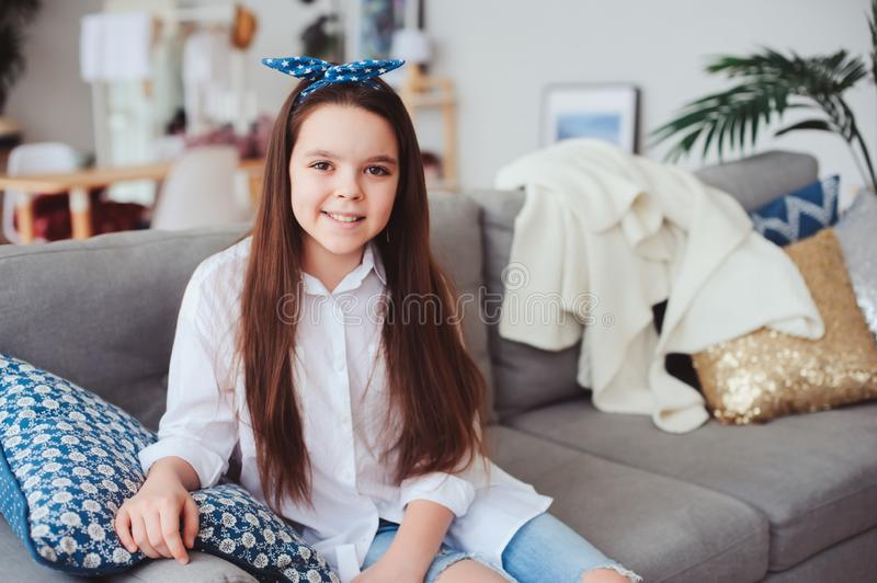 Happy 10 years old kid or preteen girl relaxing at home. Cozy living room with modern scandinavian interior, homely lifestyle weekend royalty free stock photo