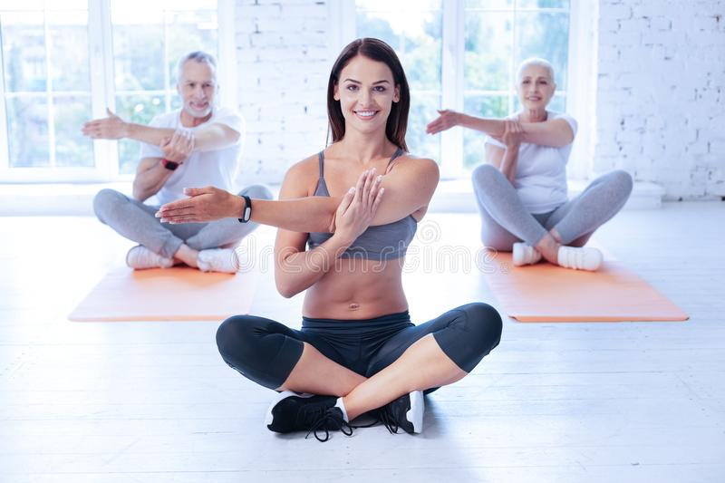 Happy yoga tutor training with her clients royalty free stock images