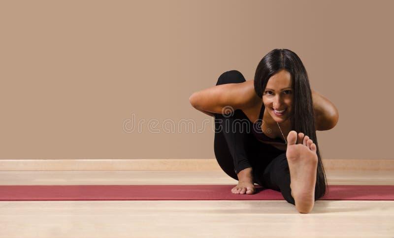 Happy yoga woman looking at camera stretching stock image