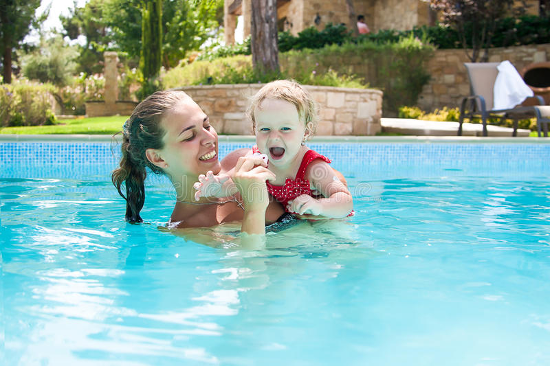Happy young active mother and curly little baby having fun in a swimming pool. Happy family, young active mother and adorable curly little baby having fun in a stock images