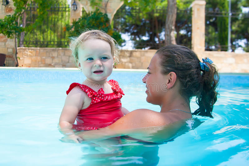 Happy young active mother and curly little baby having fun in a swimming pool. Happy family, young active mother and adorable curly little baby having fun in a royalty free stock photography