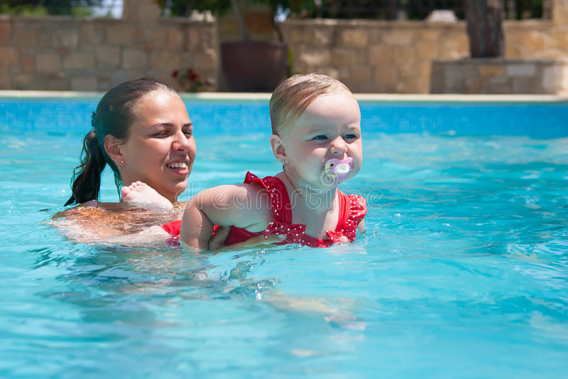 Happy young active mother and curly little baby having fun in a swimming pool. Happy family, young active mother and adorable curly little baby having fun in a stock photo