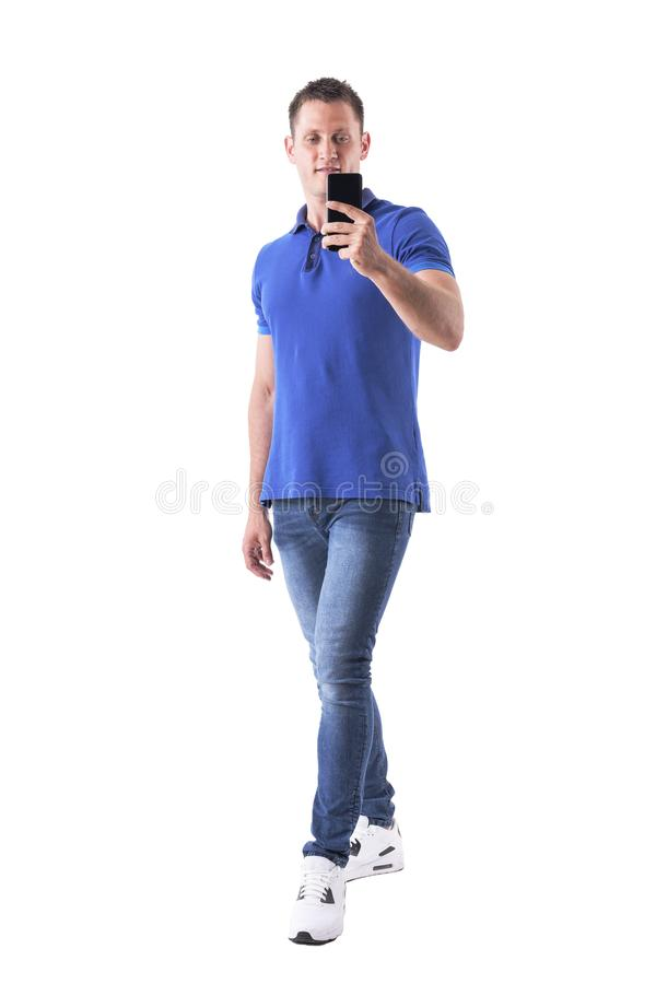Happy young adult casual man in blue polo shirt taking selfie with smart phone. Full body isolated on white background royalty free stock photos
