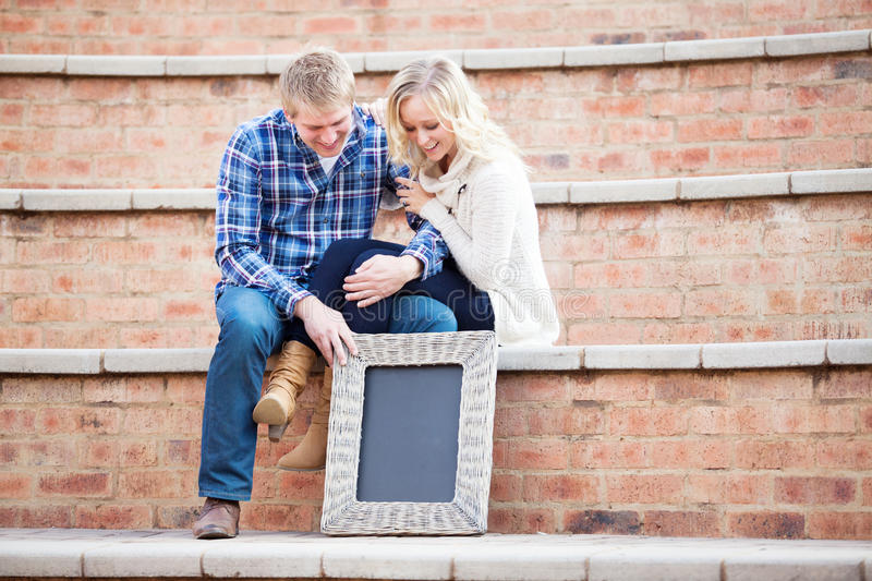 Happy young adult couple looking down at your text, focus on sign. Happy young Caucasian adult couple looking down at blackboard with your custom text, focus on stock photo