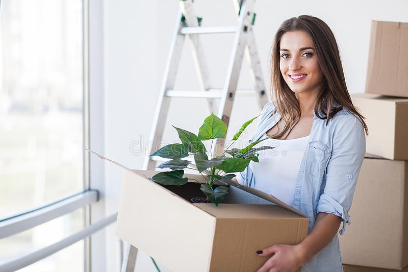 Happy Young Adult Woman Holding Moving Boxes In Empty Room In A New House. stock photography