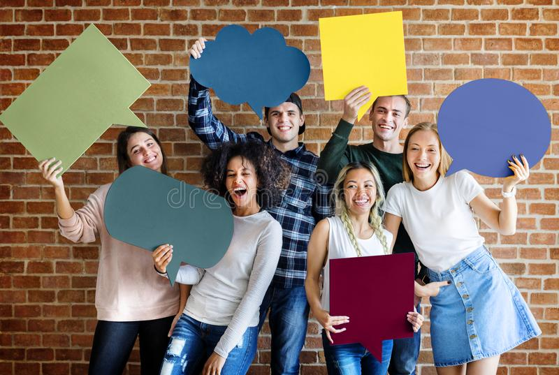 Happy young adults holding empty placard thought bubbles copyspa. Ce stock photo