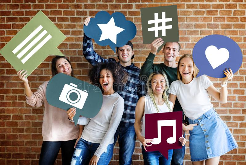 Happy young adults holding thought bubble with social medai concept icons stock image