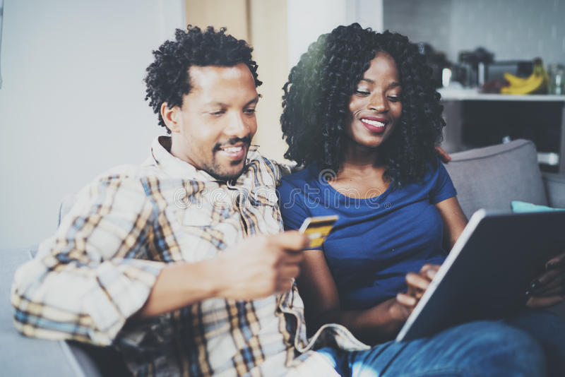 Happy young african american couple shopping online through touch tablet using credit card at home. Horizontal,blurred. Background royalty free stock image