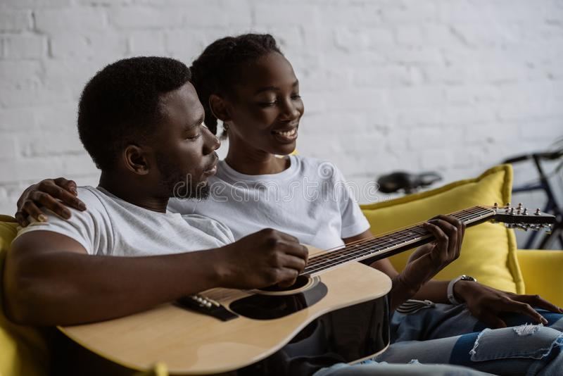 Happy young african american couple sitting together on sofa and man. Playing acoustic guitar stock image