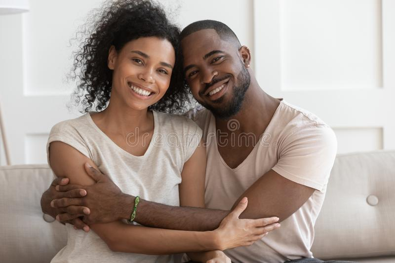 Happy young smiling cuddling african american family portrait. royalty free stock photo