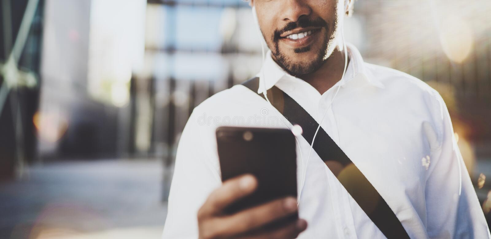 Happy young African American man in headphone walking at sunny city and enjoying to listen to music on his smart phone. Blurred background.Horizontal wide royalty free stock photos