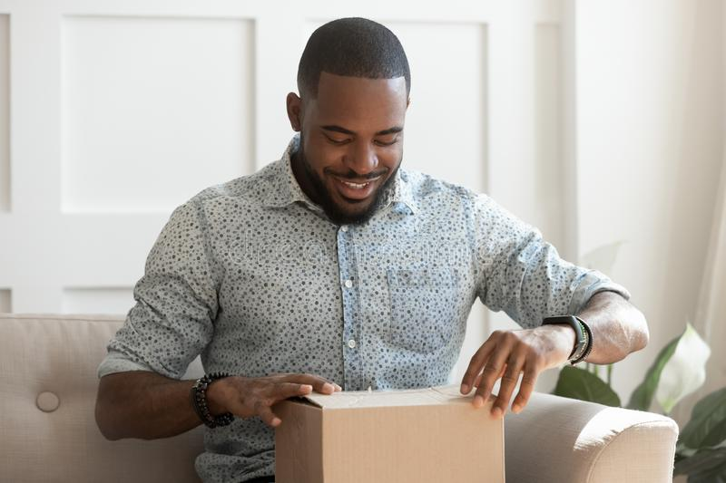 Happy young african american man unboxing delivery parcel. stock images