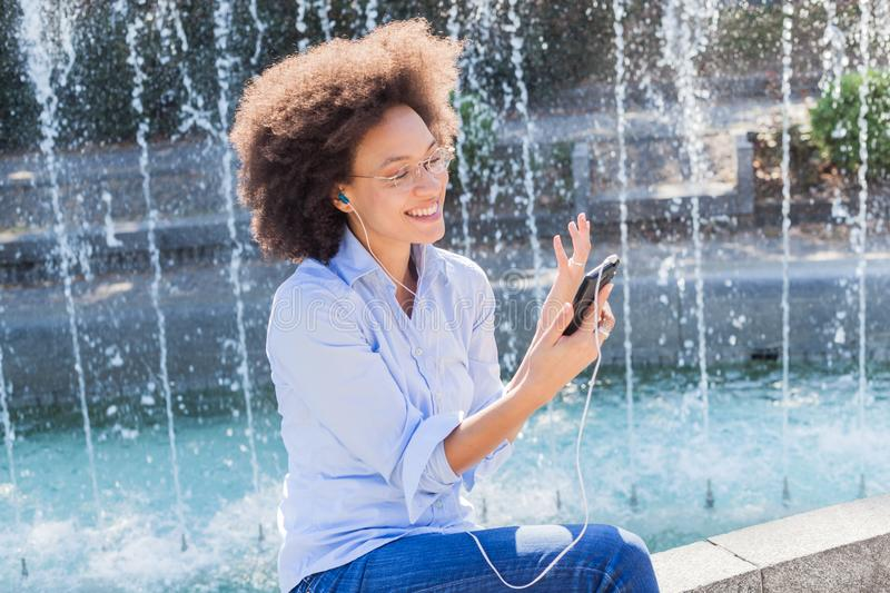 Happy Young African American Woman In Casual Wear, Using Smartphones For Social Network royalty free stock photo