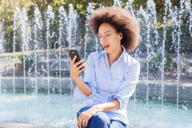 Happy Young African American Woman In Casual Wear, Using Smartphones For Social Network stock photos