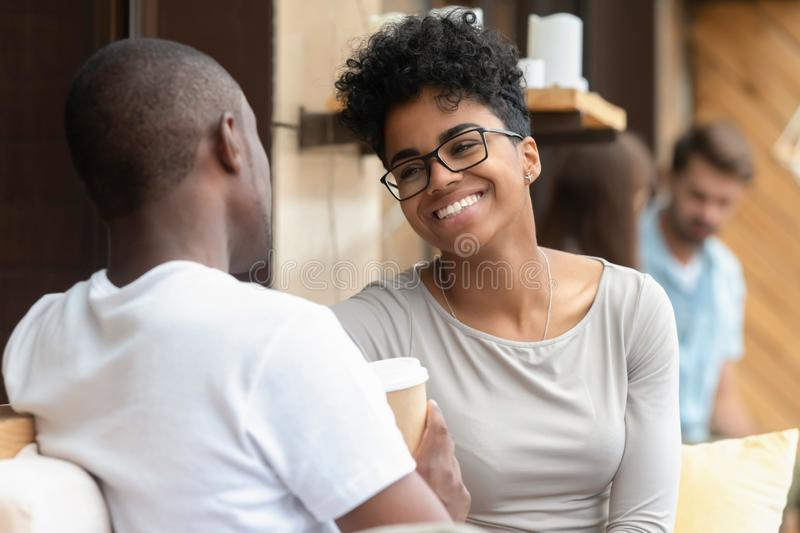 Happy young african american woman enjoy fun conversation with boyfriend. Happy young african american women smiling enjoy fun conversation with men friend royalty free stock photography