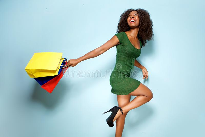 Happy young african american woman holding shopping bags on blue background royalty free stock images