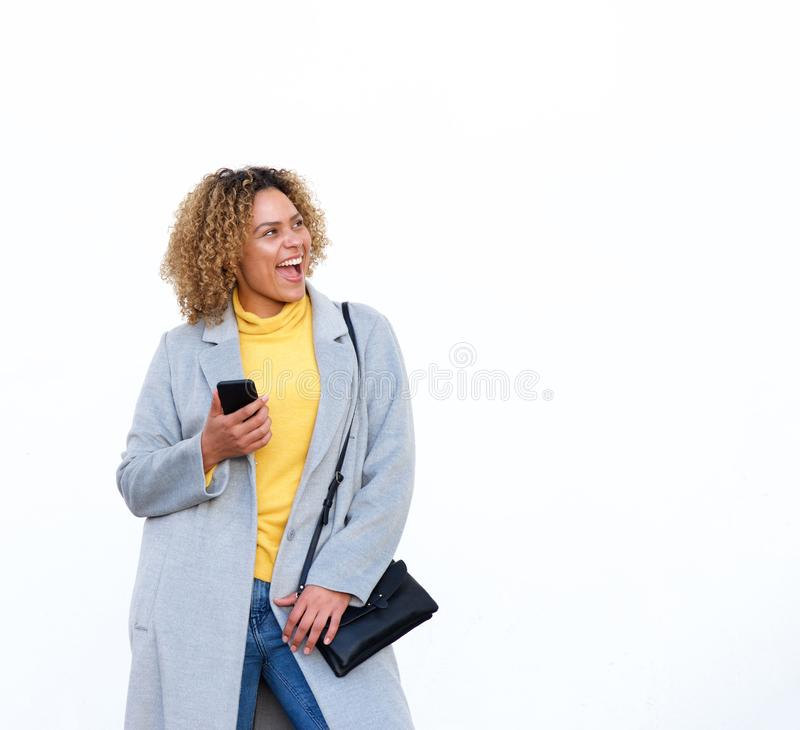 Happy young african american woman laughing against white background with mobile phone royalty free stock photo