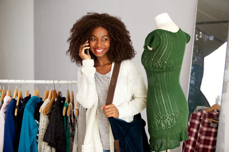 Happy young african american woman talking on phone in a clothing store stock photos