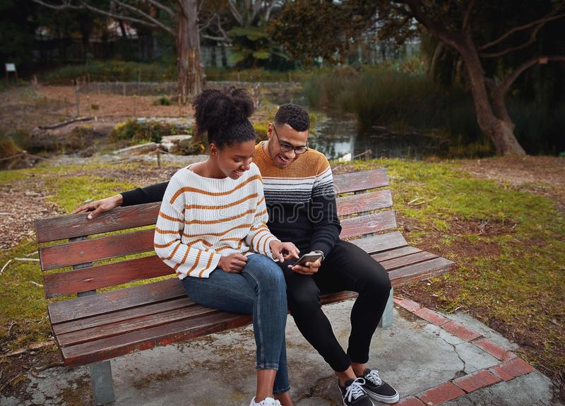 Happy young african couple sitting together on bench near pond in park using mobile phone stock photo