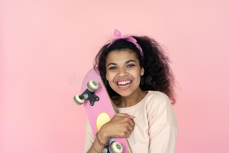 Happy young african girl laughing hold skateboard isolated on pink background. Happy smiling young african american teen girl black woman skater laughing holding royalty free stock photography