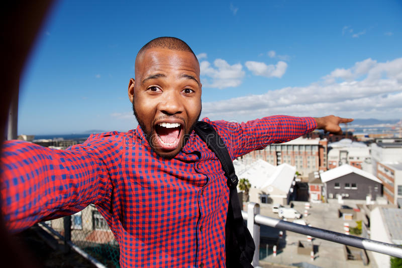 Happy young african guy pointing at the city. Portrait of happy young african guy pointing at the city stock photography