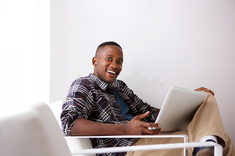 Happy young african man on arm chair with a laptop stock photography