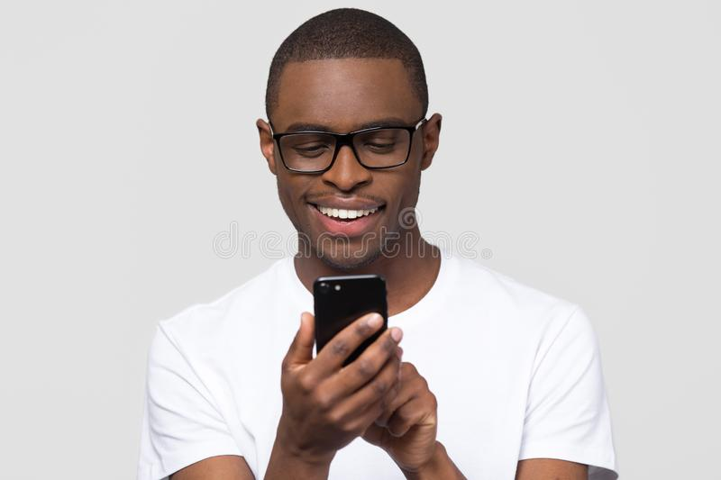Happy young african man using smartphone gadget social media apps. Happy young african american man in glasses using smartphone gadget social media apps, smiling stock photo