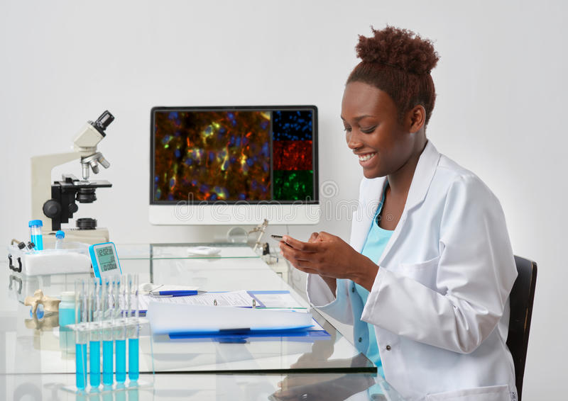 Happy young African scientist texts on her mobile phone stock image