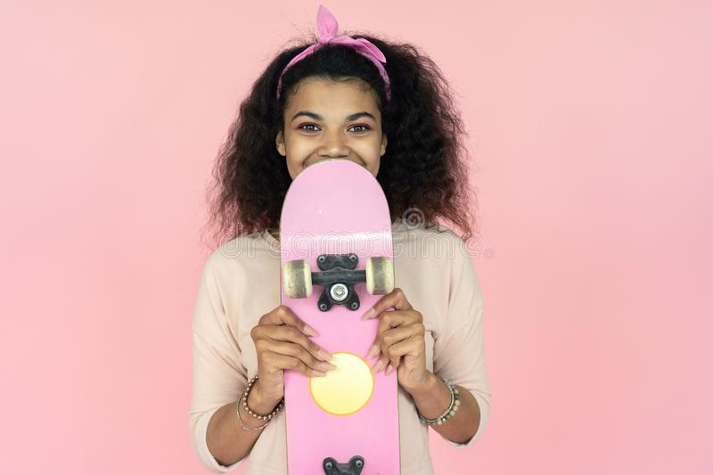 Happy young african teen girl hold skateboard isolated on pink background. Happy smiling young african american teen girl black woman skater skateboarder holding stock photography