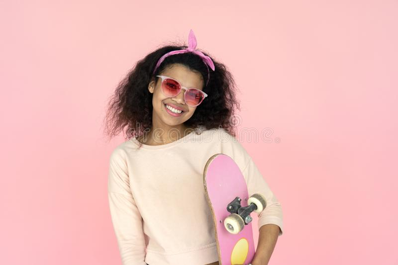 Happy young african teen girl hold skateboard isolated on pink background. Happy smiling young african american teen girl black woman skater wear glasses hold royalty free stock image
