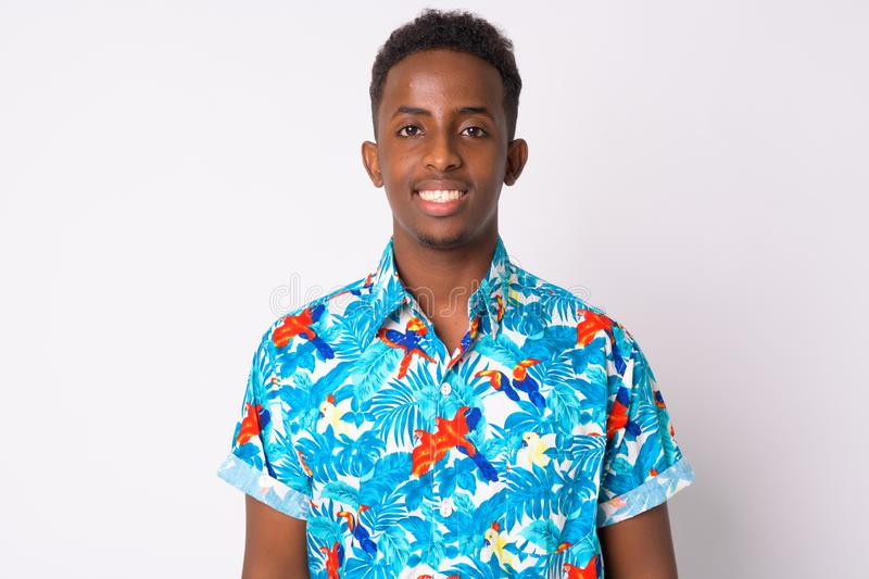 Happy young African tourist man with Afro hair smiling. Studio shot of young African tourist man with Afro hair against white background royalty free stock photography