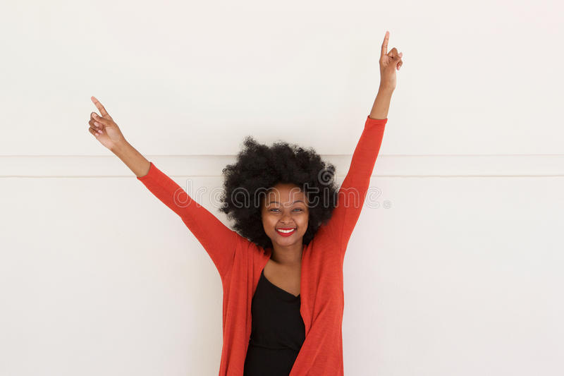 Happy young african woman with arms raised by white wall royalty free stock photography
