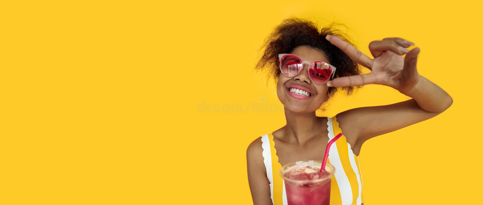 Happy young african woman hold drink wear glasses laugh look at camera. Cheerful black teen girl enjoy summer cocktail isolated on yellow studio background royalty free stock images