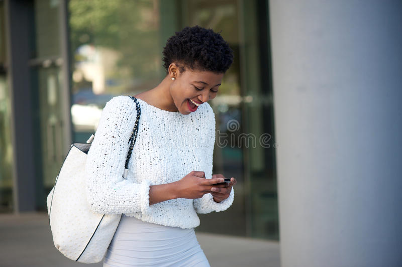 Happy young african woman reading text on cell phone stock photos