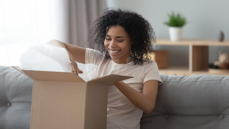Happy african woman satisfied customer open parcel sit on sofa royalty free stock photo