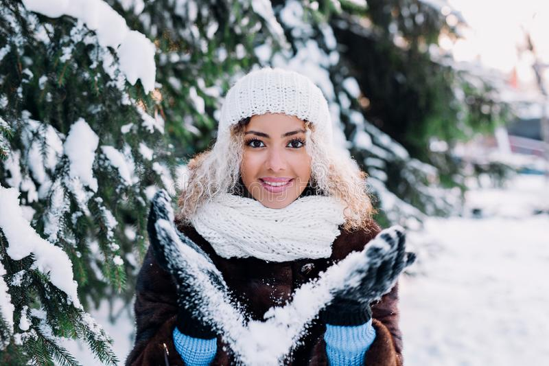 Happy young afro american woman blowing snow in winter park stock photo
