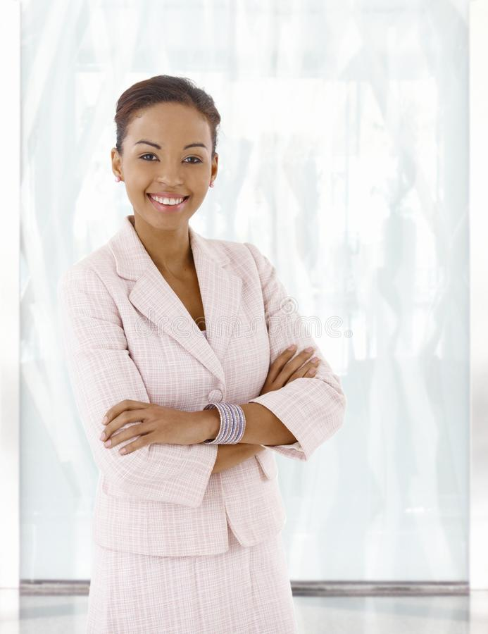 Happy young afro-american woman in office lobby. Portrait of happy young afro-american woman, looking at camera, smiling stock photos