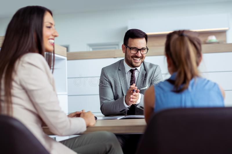 Happy agent at car salon talking to beautiful young woman and her daughter. royalty free stock photo