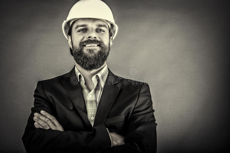 Happy young architect with hardhat and arms folded royalty free stock photo