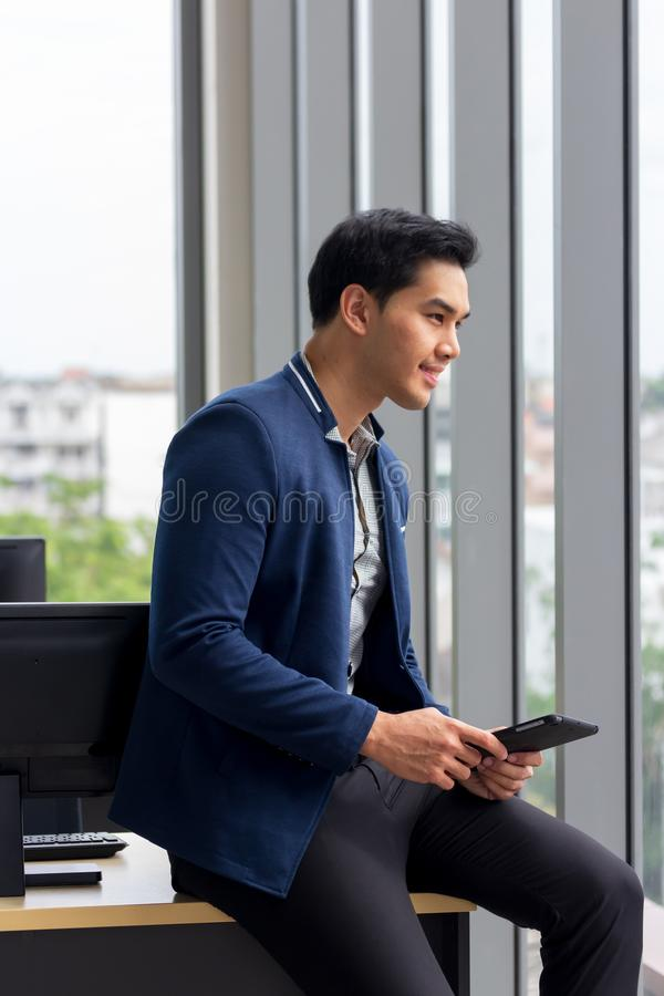 Young asian business man work and holding smartphone in modern office on computer royalty free stock photo