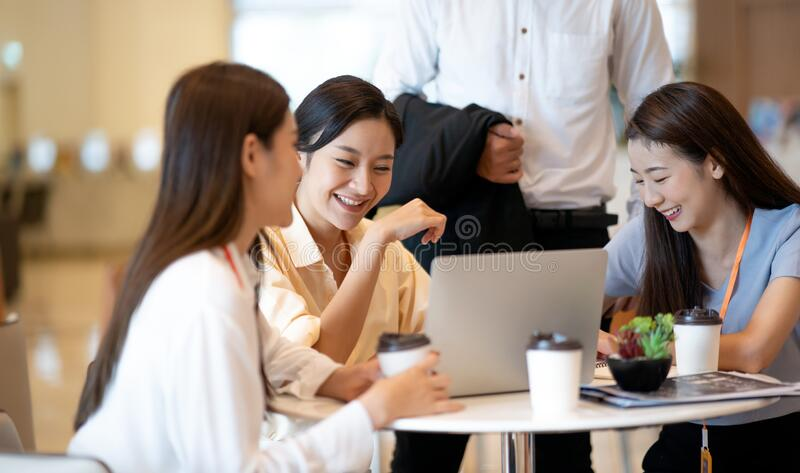 Happy young Asian business people discussing creative project Meeting Discussion with laptop in modern creative office discussion royalty free stock images