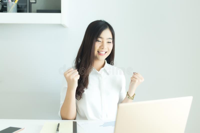 Happy young asian business woman finished her work at workplace. stock photo