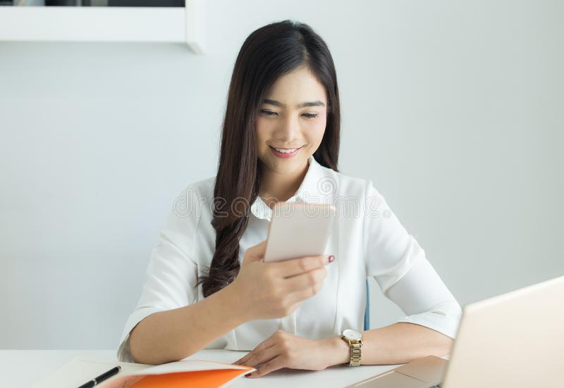 Happy young asian business woman use smartphone for working at her workplace stock photos