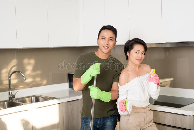 Happy young Asian couple cleaning kitchen together stock image