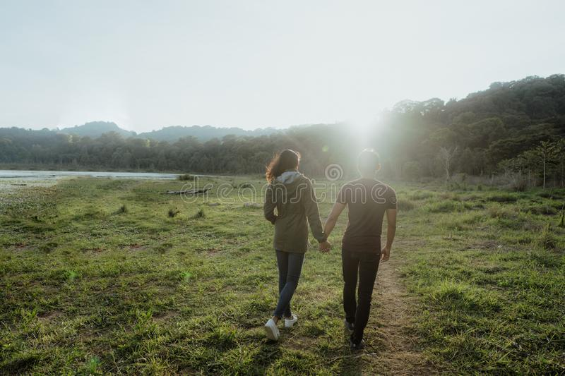Happy young asian couple in countryside enjoying nature. Portrait of happy young asian couple in countryside enjoying nature together royalty free stock photos