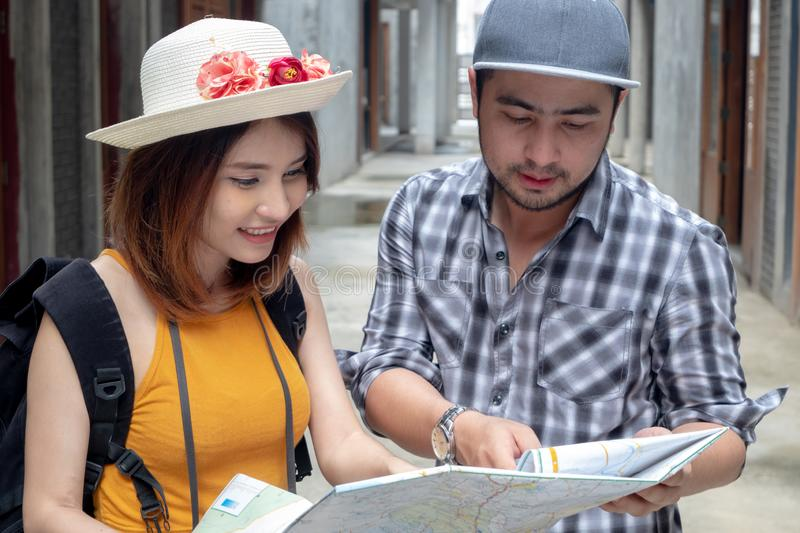 Happy young Asian couple holding map looking direction on honeymoon vacation..Tourist people on summer lost together on holiday royalty free stock images