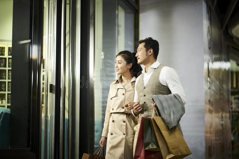 Asian couple looking into shop window royalty free stock image